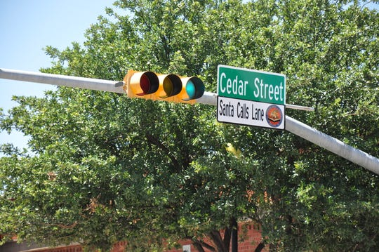 New honorary Santa Calls Lane street signs were installed Tuesday on Cedar Street in downtown Abilene.