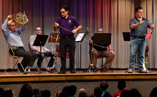 Rob Tucker holds up his French horn as Bernie Scherr attaches his trumpet mouthpiece to a length of plastic tubing being held at the other end by tuba player Jeff Cottrell. The members of Key City Brass were showing children at the Abilene Public Library how long the tubing on Tucker's instrument would be if unrolled. The other members of the group are trumpet player David Amlung and trombonist Clay Johnson, all performed in the Young Audiences series at the library's main branch Tuesday.