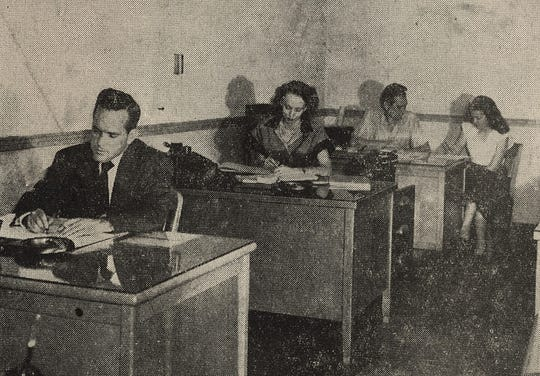 "J.D. Perry, whose name eventually would be added to company name, works at his desk in what was called a ""modern air conditioned office"" at Cox Hunter Hall Insurance in 1949. Hunter was a partner in the firm and supervised the claims department. At back of the room, is Elbert Hall, said to be dictating ""an important letter"" to Pat Hendley."