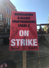 Workers of RAM Construction have been holding these signs outside The Milton for six days.