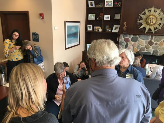 Attendees at Tuesday's Housing Kitsap board meeting huddle around phones in the agency's lobby watching a livestream of the board's meeting after they weren't allowed in the meeting room.