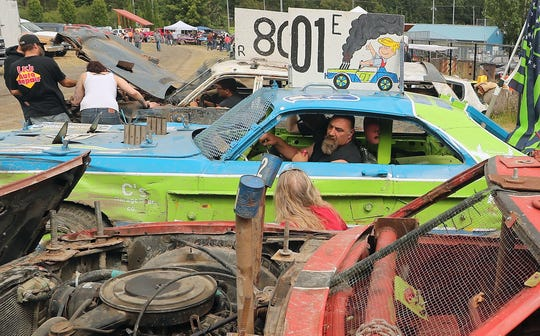 Dennis Trueax chats from the window of his car, which is parked in between his sons, Dennis Jr. and Moana's derby cars, prior to the start of the speed trials for the Kitsap Destruction Derby at Thunderbird Stadium on Saturday, June 22, 2019.