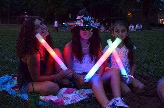 Revelers provide their own lighting during a Vineland Fourth of July fireworks show.