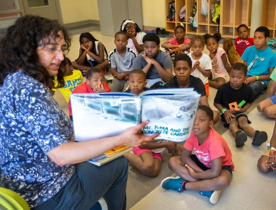 Elisa Gallon, the children's librarian for the Price Hill branch, reads a book to children.  As Gallon read, 'Me, Tom and the Concrete Garden', the children listened with rapt attention, occasionally asking a question.