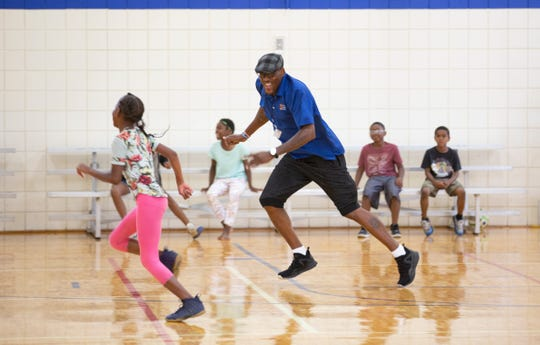 Eriyonna Jones runs from Tanaruse Witherspoon, 'Spoon' to anyone who knows him, during Sharks and Minnows with his day campers at Price Hill Recreation Center. The camp, from 11- 3pm daily, includes lunch from Cincinnati Public Schools.