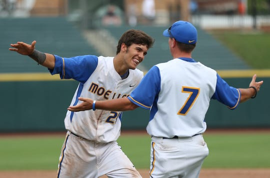 Riley Mahan runs to give head coach Tim Held a big hug after the final out of the Crusaders' 7-1 victory over Cleveland St. Ignatius in Columbus on Sunday. The title was Moeller's second straight and seventh overall Sunday, June, 9, 2013.