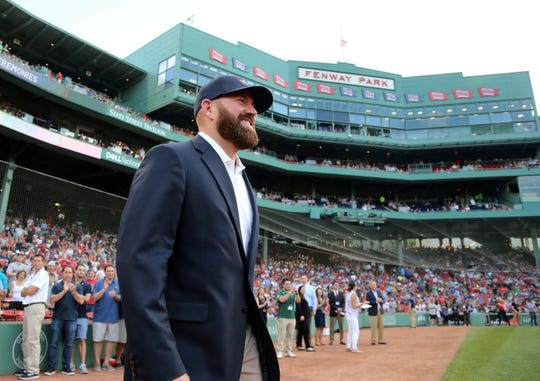 Former Boston Red Sox player Kevin Youkilis walks onto the field as Red Sox Hall of Fame inductees are honored before an interleague baseball game against the Atlanta Braves at Fenway Park, Friday, May 25, 2018, in Boston.