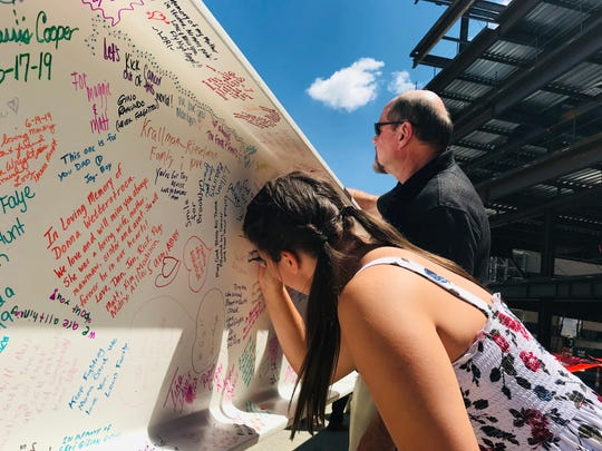 """Lexi McMillin, 12, of Hebron, and her grandfather Gary Baker sign the last beam to go into the new cancer center at St. Elizabeth Healthcare Edgewood. The traditional """"topping-out"""" ceremony was Tuesday. Baker's wife, Stephanie, a breast-cancer survivor, is the head of the patient advisory council for the new center."""