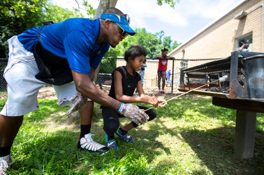 Verniyah Sherrer, 11, gets a lesson in how make s'mores from Tanaruse Witherspoon, 'Spoon' to anyone who knows him, during day camp at Price Hill Recreation Center. The center offers special activities each day. The kids also have field trips each week.