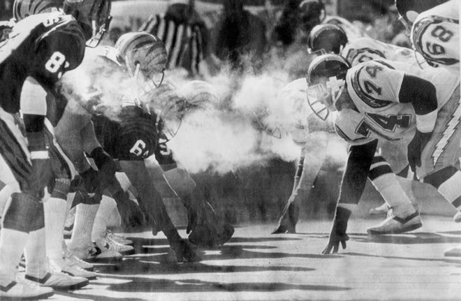 """JANUARY 10, 1982: Linemen for the Cincinnati Bengals, left, and the San Diego Chargers line up in sub-zero temperatures during the AFC Championship Game on January 10, 1982, in what was dubbed """"The Freezer Bowl"""" at Riverfront Stadium. Playing in 9 below zero temperatures and wind gusting to 40 miles per hour, the Bengals downed the Chargers 27-7."""