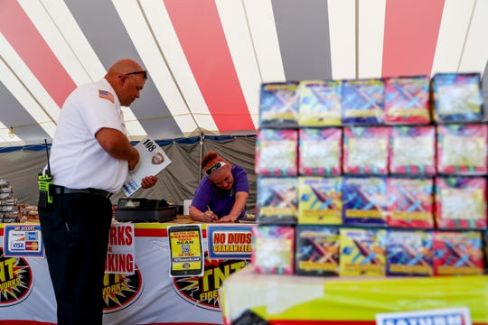 Candi Coleman signs off on an inspection of her fireworks tent at the TNT Fireworks tent at Madison Street and Memorial Drive in Clarksville, Tenn., on Tuesday, June 25, 2019.