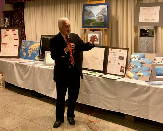 Sy Mayerson, EMAP founder, chairman and CEO, speaking about the students' achievements at the program's graduation on June 12 at III Amici Ristorante in Linden. Behind him are marketing materials that students created to help their visions become reality.