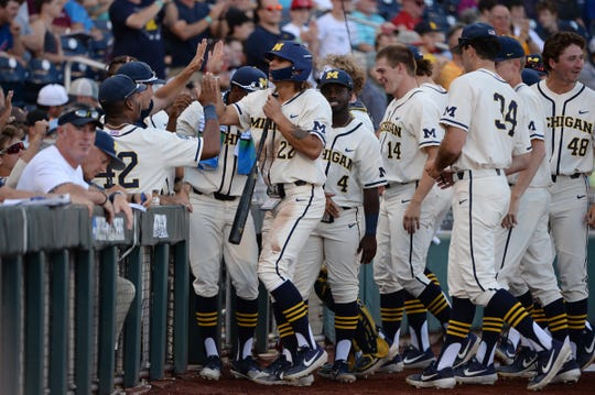 Michigan Wolverines right fielder Jordan Brewer celebrates with teammates after scoring a run against the Vanderbilt Commodores during the first inning in Game 1 of the championship series of the 2019 College World Series at TD Ameritrade Park, June 24, 2019, in Omaha, Neb.