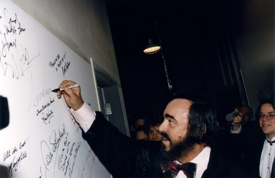 Luciano Pavarotti signing the autograph wall backstage at the Detroit Opera House in 1996.