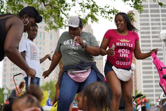 Shawnese Williams (left) of Detroit dances  with Keisha Thompkins (right) of Detroit waiting for the start of the 2019 Ford Fireworks at Hart Plaza in downtown Detroit on Monday, June 24, 2019.