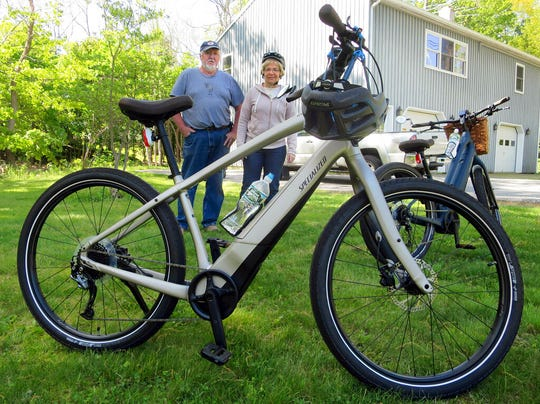 In this June 8, 2019 photo, Gordon and Janice Goodwin show their electric-assist bicycles outside their home in Bar Harbor, Maine. The bikes are banned on carriage roads and bicycle paths in nearby Acadia National Park.