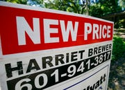 "A house on the market has a ""new price"" sign fixed on the realtor's sign in northeast Jackson, Miss."