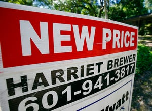 """A house on the market has a """"new price"""" sign fixed on the realtor's sign in northeast Jackson, Miss."""