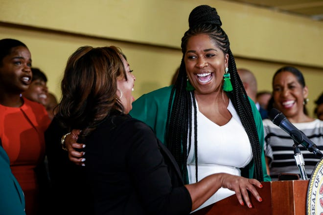 Rep. Jehan Gordon-Booth, D-Peoria, right, laughs with Illinois State Sen. Toi Hutchinson, D-Olympia Fields, left, during a news conference before Gov. J. B. Pritzker signs a bill that legalizes adult-use cannabis in the state of Illinois.