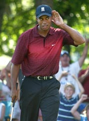 Tiger Woods makes a long putt on No. 17 at Warwick Hills during the 2005 Buick Open and asks for more noise.