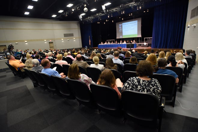 The audience listens as the Grosse Pointe School Board discusses school reconfiguration plans Monday.