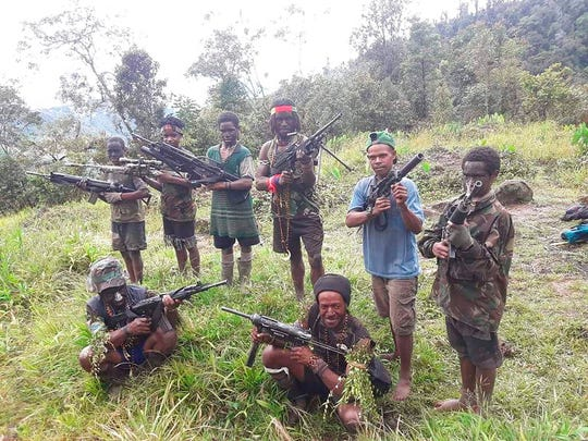 In this photo taken in May 2019, and released by the West Papua Liberation Army-Free Papua Organization, men and boys from the West Papua Liberation Army pose with weapons in the Nduga region of the central highlands, Papua province, Indonesia.