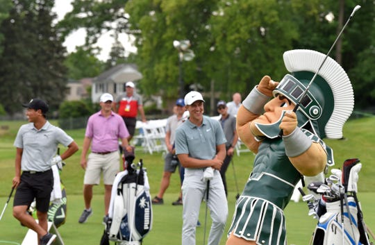 Sparty takes a swing at a junior golf clinic last summer in Detroit.