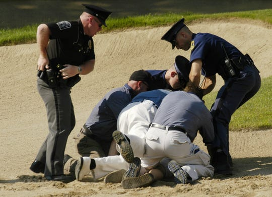 Security personnel tackle a fan on the No. 17 hole at Warwick Hills during the 2004 Buick Open. The fan was attempting to jump into the pond next to the green.