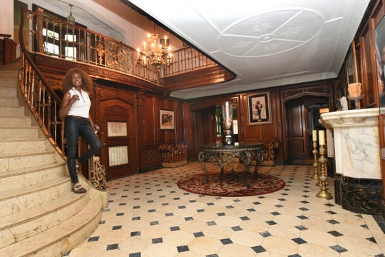 Judith Doss descends the stairs into the foyer at her Palmer Woods home, which she has made available as a bed and breakfast rental for $1,875 a night for the Rocket Mortgage Classic.