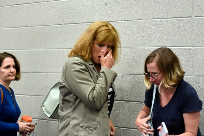An unidentified woman cries after finding out that two Grosse Pointe elementary schools, Robert Trombly Elementary and Charles A. Poupard Elementary, are now due to be closed after it was voted on by the GP Board of Education, Monday, June 24, 2019, in Grosse Pointe Farms, Mich.  (Jose Juarez/Special to Detroit News)
