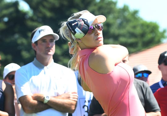 Bubba Watson watches as Paige Spiranac drives off the 15th tee to start the competition.