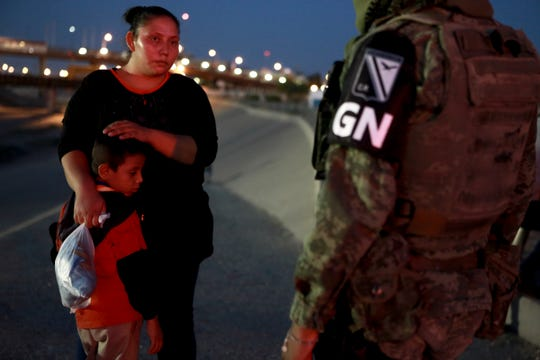 A military police officer, wearing the insignia of Mexico's new National Guard, detains Guatemalan migrants to keep them from crossing from Juarez, Mexico to El Paso, Texas, late Monday, June 24, 2019.