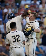 Michigan's Jimmy Kerr, right, celebrates after hitting a 2-run home run against Vanderbilt during the seventh inning of Game 1 of the NCAA College World Series baseball finals in Omaha, Neb., Monday, June 24, 2019.