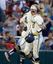 Michigan's Joe Donovan (0) celebrates with Ako Thomas (4) after hitting a home run against Vanderbilt during the eighth inning in Game 1.