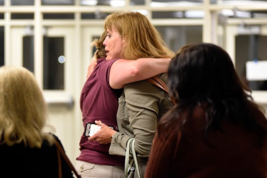 Two unidentified women hug after finding out that two Grosse Pointe elementary schools, Robert Trombly Elementary and Charles A. Poupard Elementary, are now due to be closed.