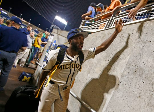 Michigan left fielder Christan Bullock greets fans as he leaves the field after Michigan defeated Vanderbilt in Game 1 of the College World Series.