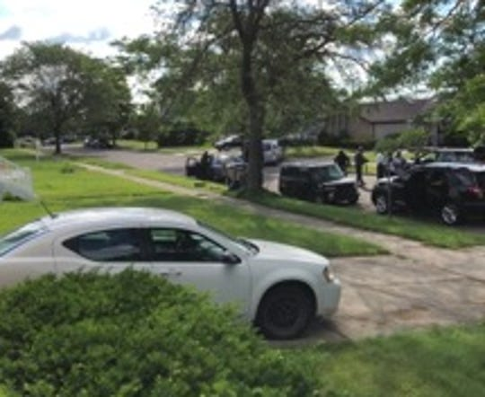 Police gather at a Highland Park house where a gunman is barricaded Tuesday.