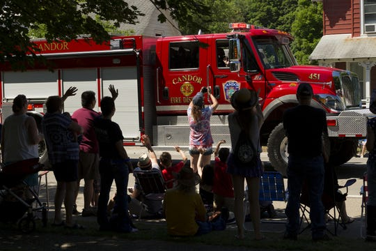 Spectators wave as the last few fire trucks made their way along Main Street during the annual Candor Fourth of July parade in 2016.