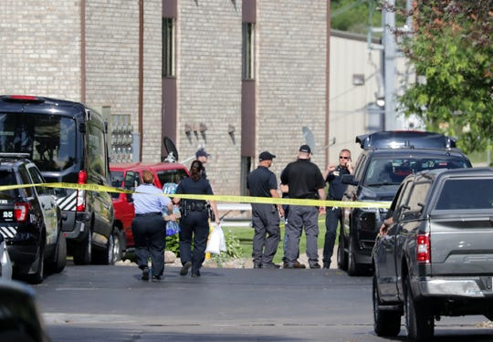 Officers gather to investigate a fatal police shooting of a Menasha man at his apartment in the 900 block of Tayco Street.