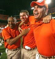 Clemson coach Dabo Swinney, center, hugs team administrator Woody McCorvey, left, and assistant coach Danny Pearman, right, after the Tigers beat Miami 40-37 in overtime in 2009.