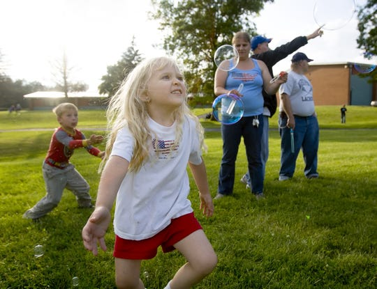 James Harriger, left, and Kailey Riemer, center, chase after bubbles blown by Tammy Reimer during Groton's Independence Day Celebration at Groton Elementary School in 2009.