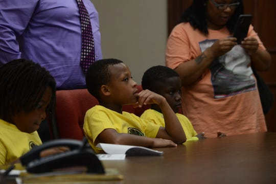 Gerkell Brooks, 11, Gerleek Triplett, 8, and Quantravious Woods, 10, listen to Councilman Johnny Lee Dodd talk about starting a business in Jackson City Hall in Jackson, Tenn. on June 25, 2019.