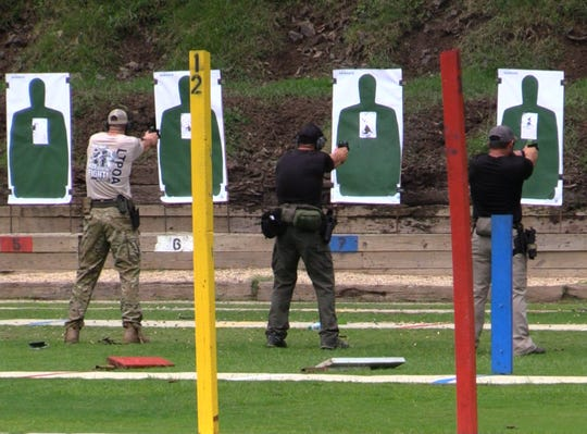 Officers practicing with pistols on paper targets