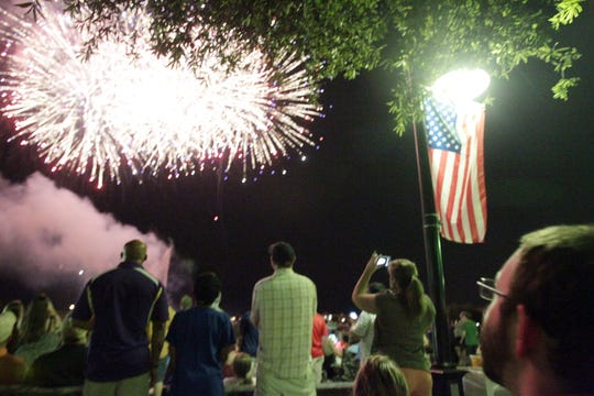 Spectators watch fireworks during the Sugar Mill Pond Independence Day celebration Thursday, July 3, 2014, in Youngsville, La.