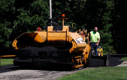 Lancaster Department of Transportation employees pave Ellwood Avenue Tuesday, June 25, 2019, in Lancaster.