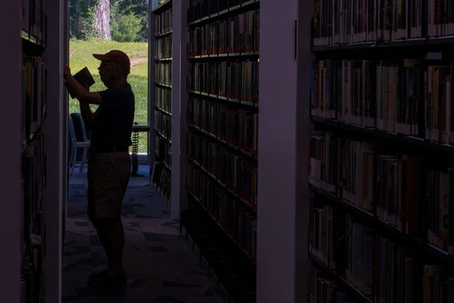A patron browses books inside the new Northeast Regional Louisville Free Public Library. June 25, 2019