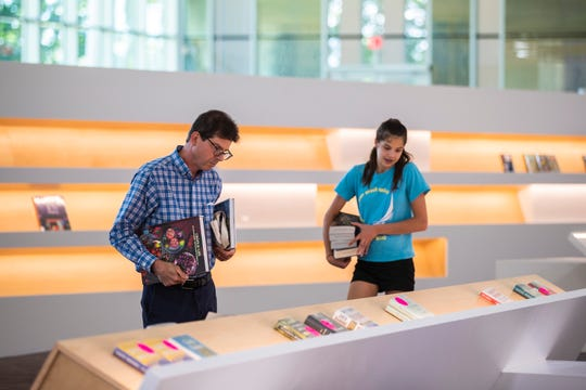 Richard Spalding, left, and his daughter, Virginia Spalding browse books inside the new Northeast Regional Louisville Free Public Library. June 25, 2019
