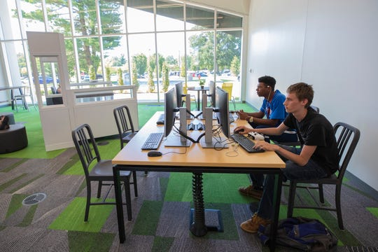 Deval Paul, from right, and Gabriel Tarver play computer games in the computer and lounge space at the new Northeast Regional Louisville Free Public Library. June 25, 2019