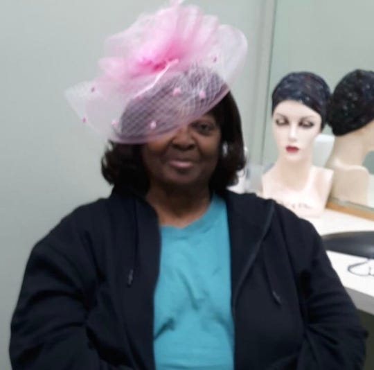 Jessie Davis of Macon, Georgia tries a wig and pink fascinator at Elegante Studio in Frandor June 20, 2019. Davis bought a pricey wig for a total stranger that day.