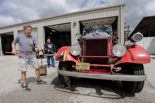 Jeff Keehan, left, and retired fireman Carl Kuehn and give the truck a good rinse outside of Manitowoc Fire Department station Thursday, May 23, 2019, in Manitowoc, Wis. The two spent many long hours getting the truck in running condition in time for the Memorial Day parade. Joshua Clark/USA TODAY NETWORK-Wisconsin